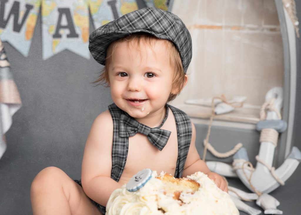 little boy with bow tie and flat cap first birthday cake