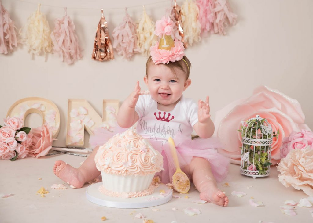 baby with a spoon and an enormous cake