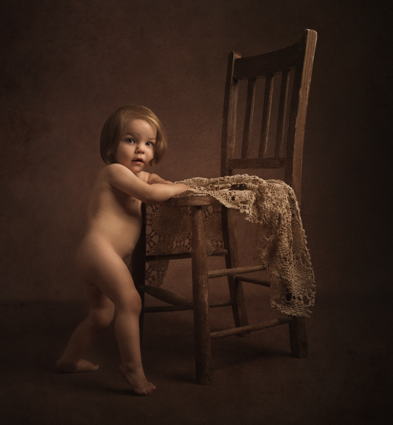 baby girl standing by chair