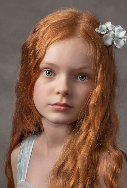 young girl with red hair and flowers in her hair