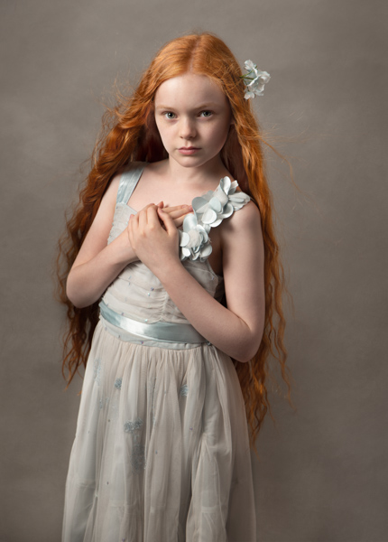 young girl with red hair in a blue dress