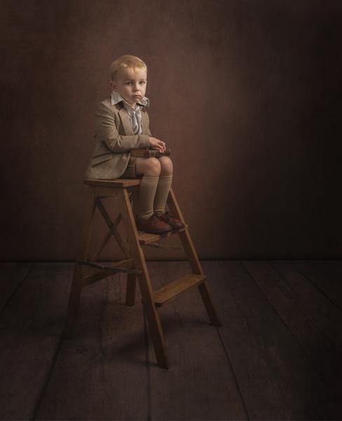 young boy sitting on a stepladder