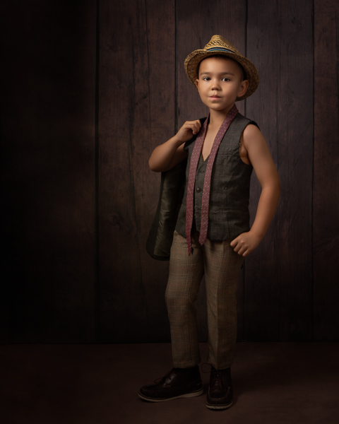 baby with a fedora and undone tie posing for a fine art photography session