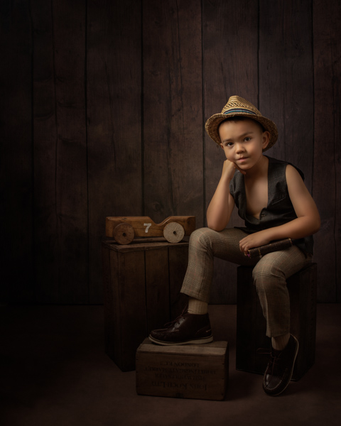 Young boy with wicker fedora sitting for fine art photography session