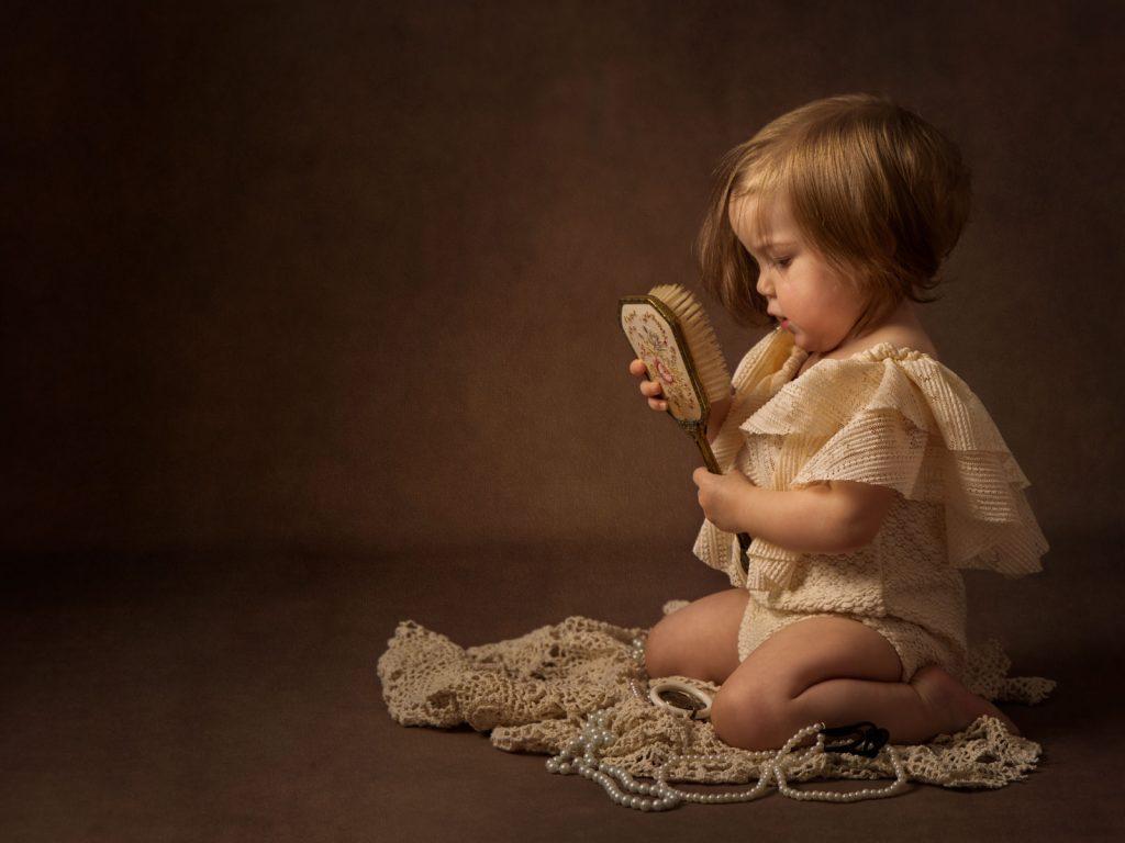beautiful baby girl holding antique hairbrush