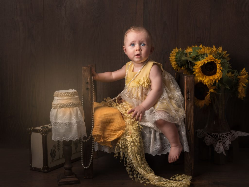 baby with pearl necklace and sunflowers fine art photoshoot