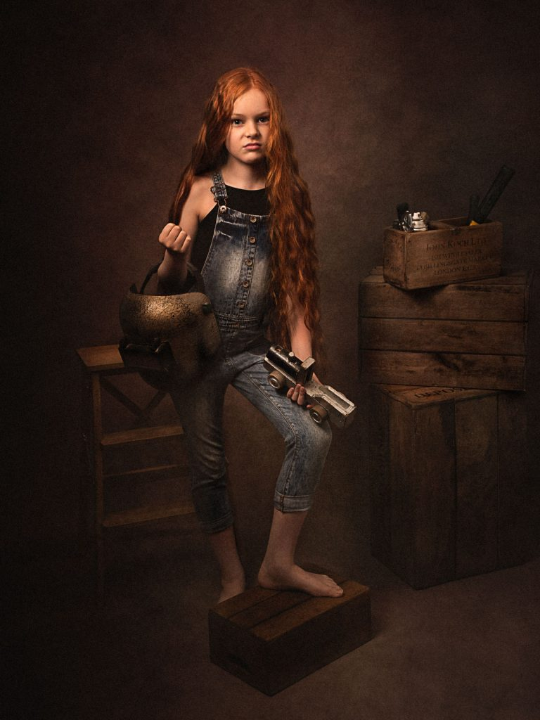 old style blacksmith child in dungarees