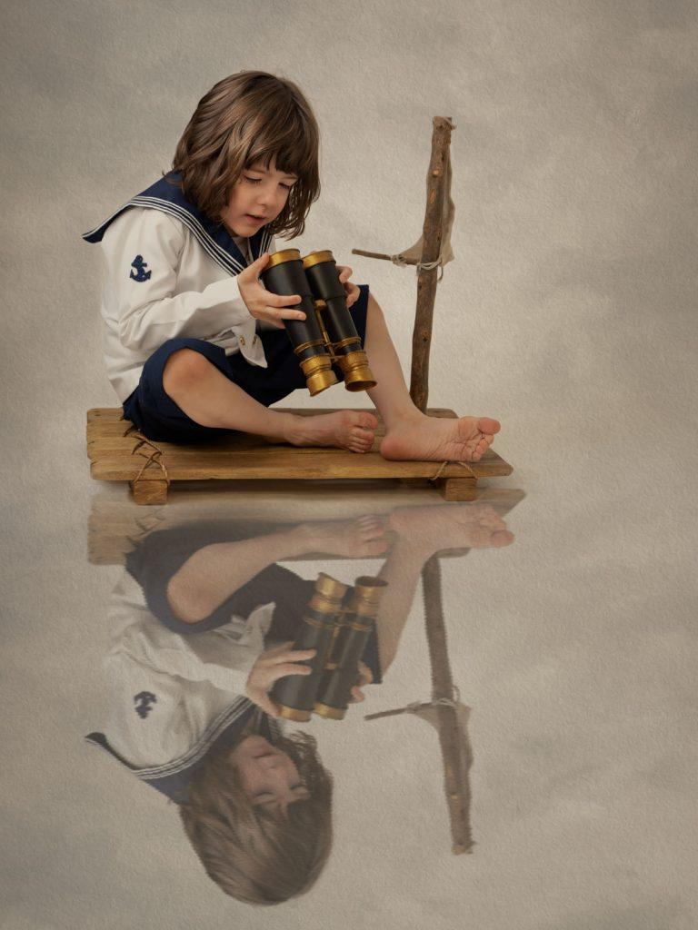 boy on a raft with binoculars fine art photoshoot