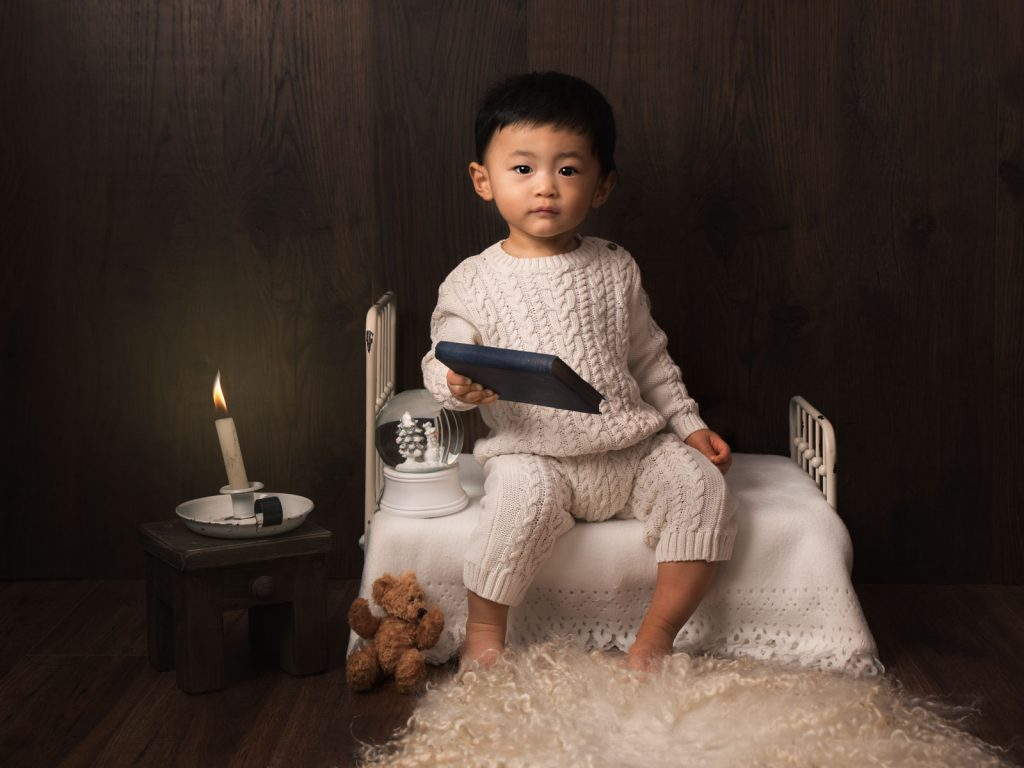 lovely boy with snow globe and a little bed fine art photoshoot