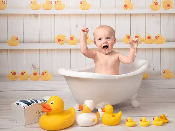 Gorgeous baby birthday photoshoot with ducks in a tub