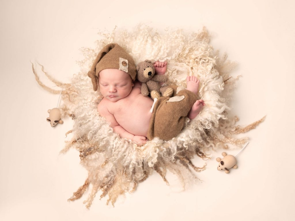 newborn baby with bear and toys