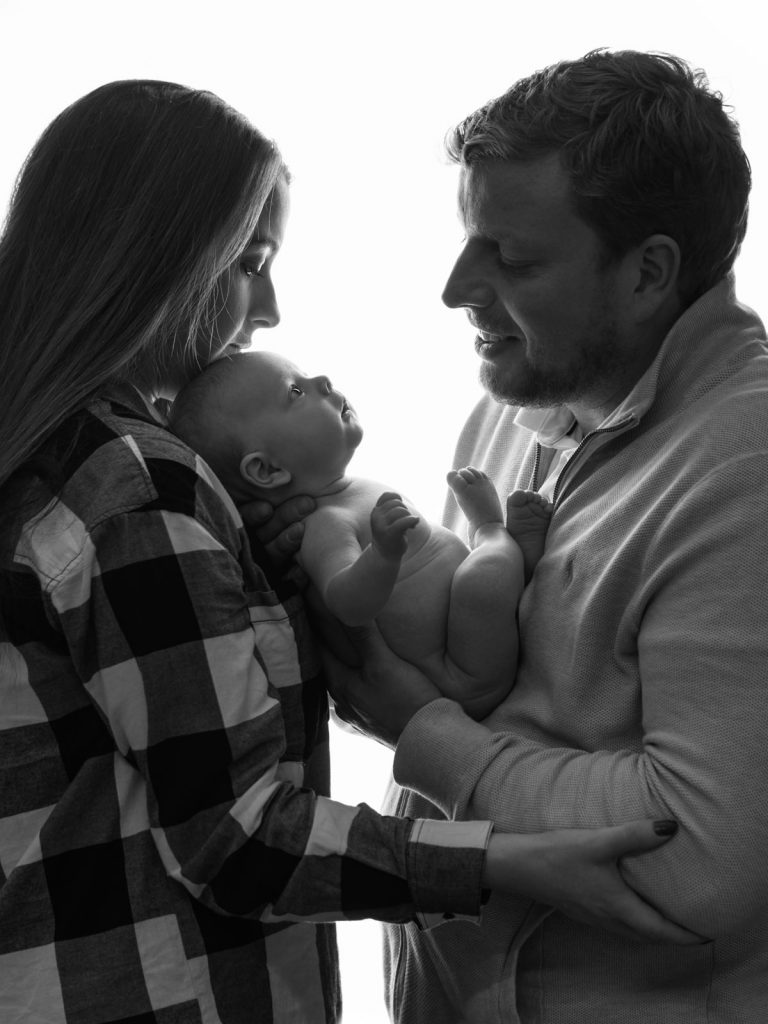 newborn baby with mum and dad together black and white photo