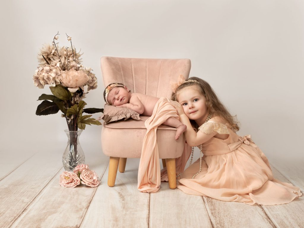 newborn baby in chair and older sister next to her
