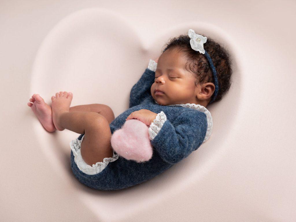 newborn baby in a heart shape prop