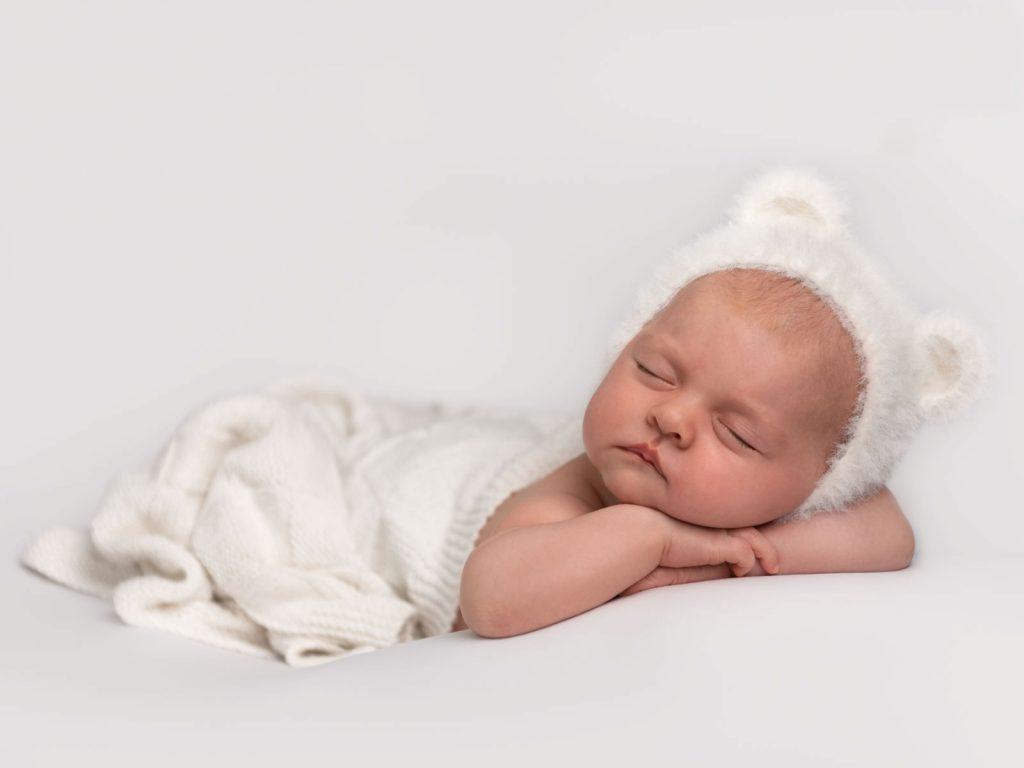newborn baby asleep with bear ears