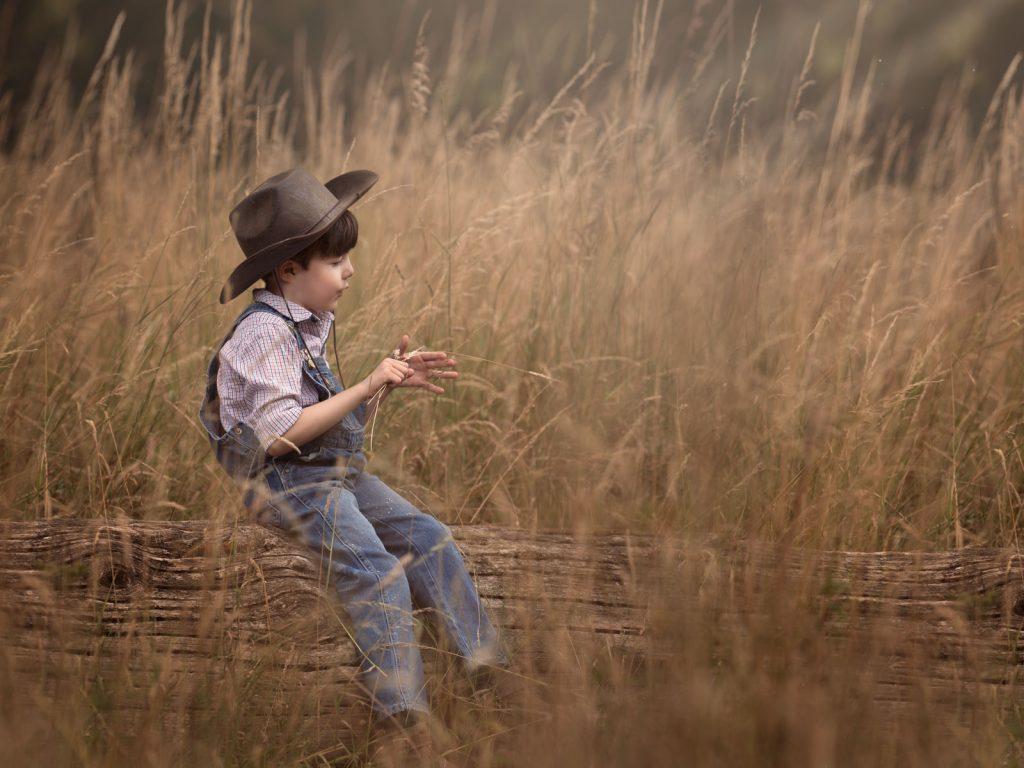 child farmer sat on a log location photoshoot