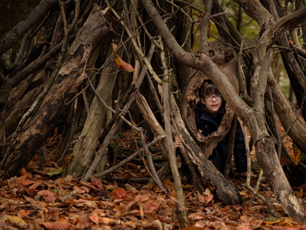 child playing hide and seek in the woods