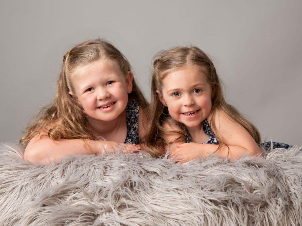 two sisters lying on a shaggy run studio photoshoot
