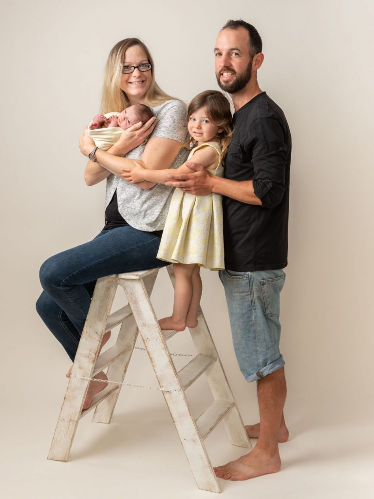 ladder with mom sat on it holding her newborn baby