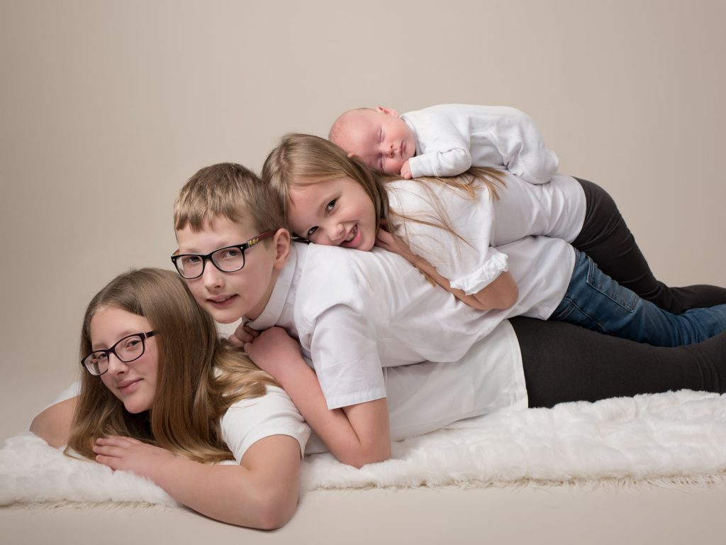 piled onto one another children and siblings together with newborn baby on top