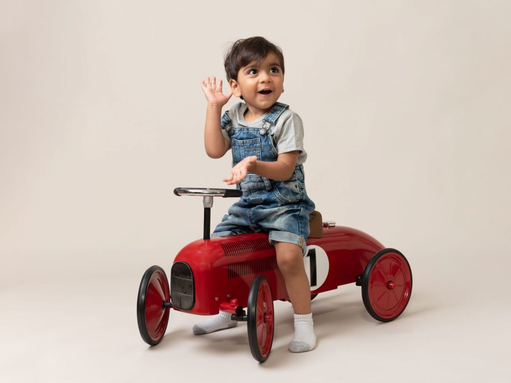 little boy in dungarees on toy car