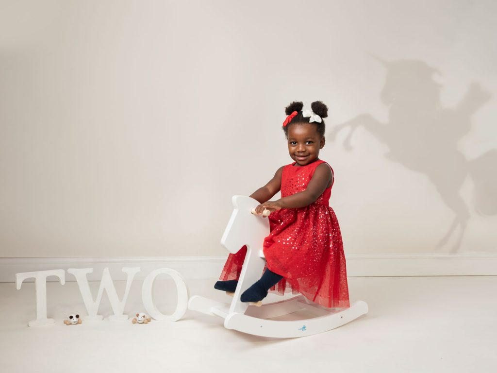 little girl in red dress on a white rocking horse studio photoshoot