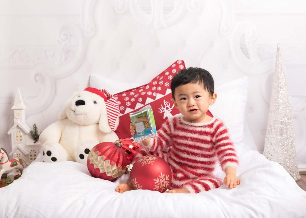 red and white with baubles toddler waiting for Santa Christmas photoshoot