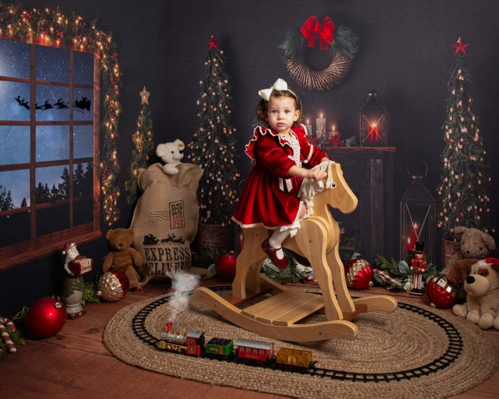 red dress girl with a rocking horse Christmas photoshoot