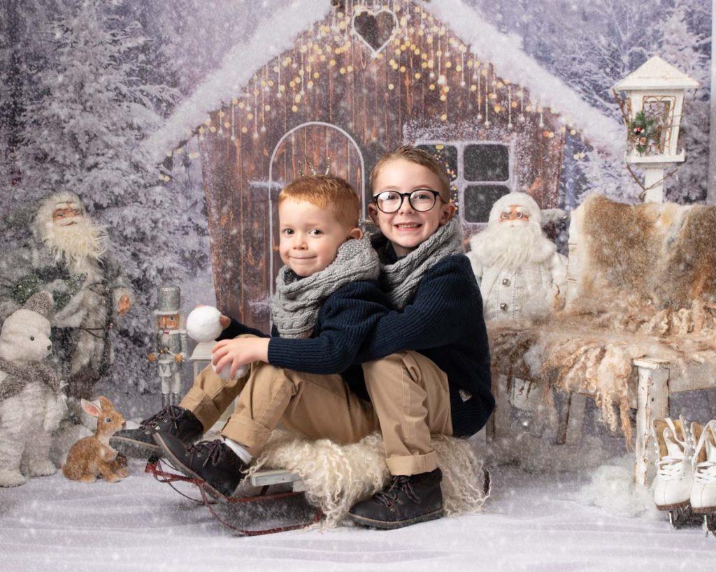 brothers sitting on a sleigh Christmas photoshoot