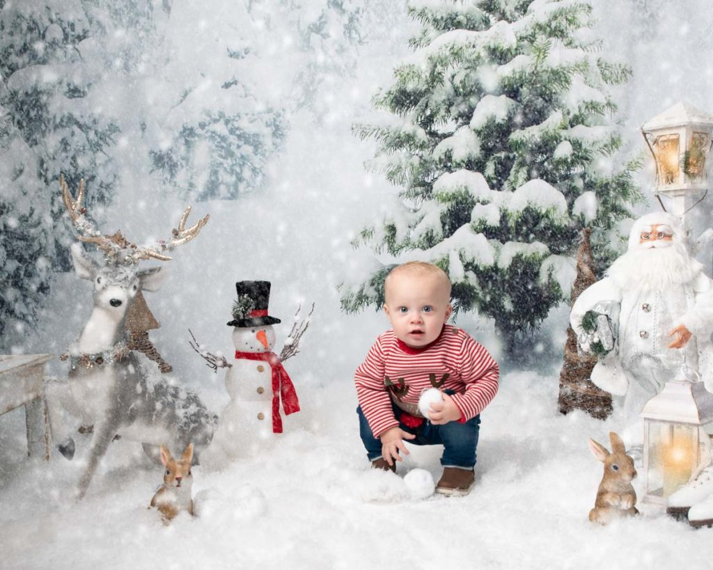 outside in the snow building a snowman toddler Christmas photoshoot