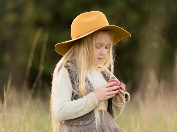 young girl with blonde hair outside location shoot wearing stylish hat