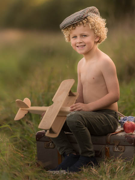 outdoor location photoshoot with young boy in autumn with plane