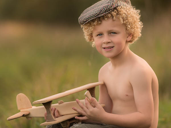 outdoor location photoshoot with young boy in autumn holding wooden plane