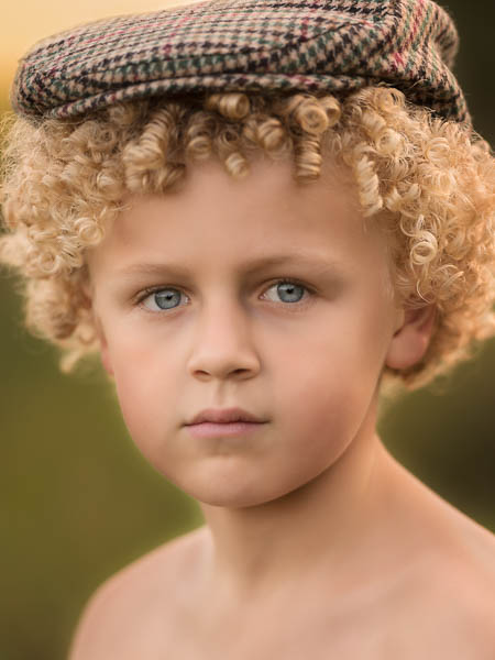outdoor location photoshoot with young boy in autumn close up with flat cap