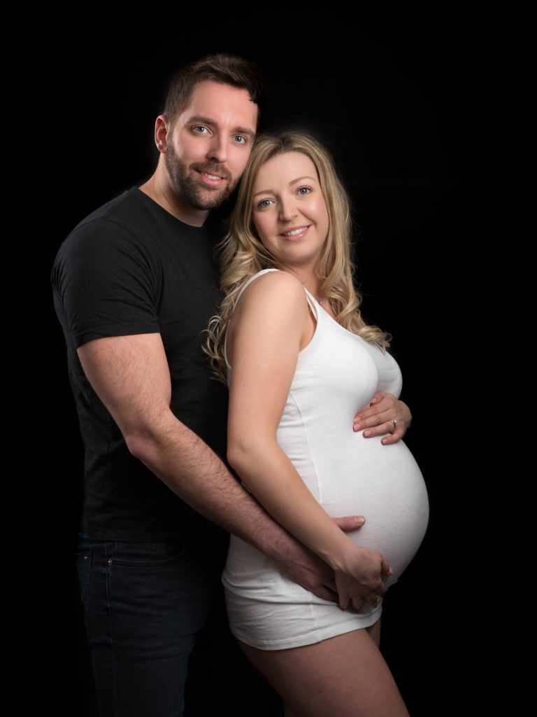 pregnant mother with her partner with dark background