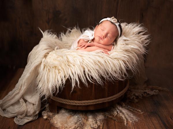 textured photoshoot of newborn baby in wooden barrel