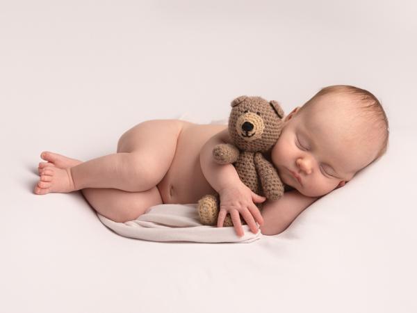 baby asleep with teddy bear newborn photoshoot
