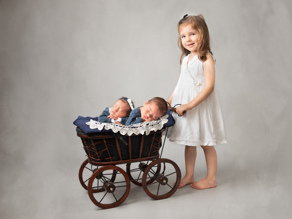 sister pushing twins in old style pram