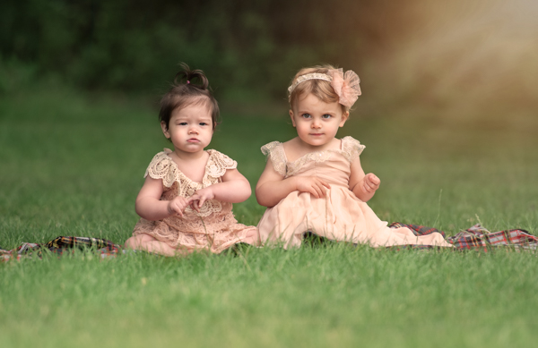 two baby girls in dresses on the grass