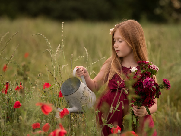 red haired girl in a field of poppies