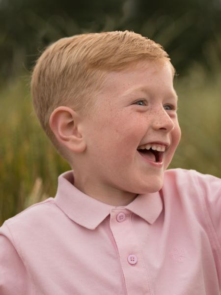 happy boy in a pink shirt