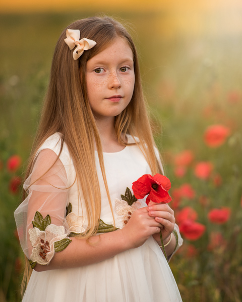 girl with a bow in her hair in a field and a poppy