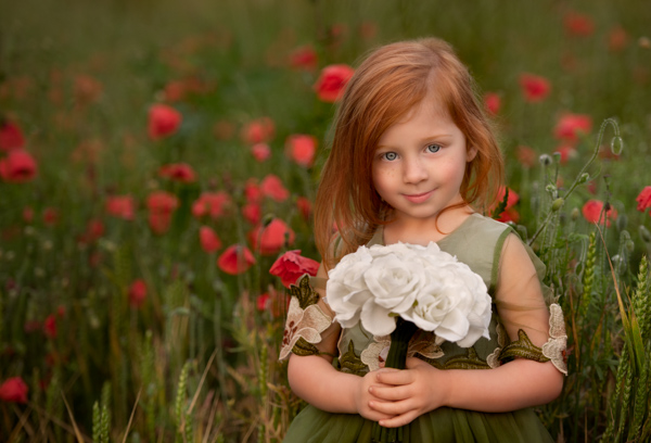 girl in a poppy field with a bunch of flowers