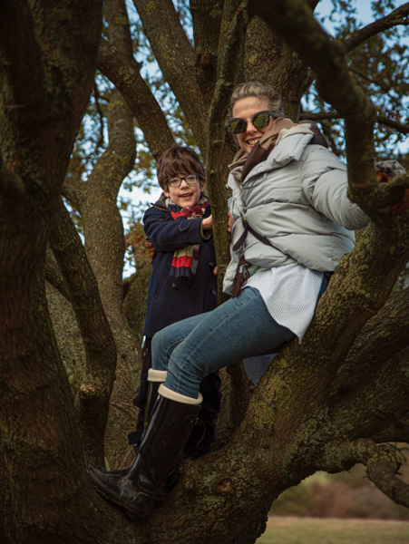 mother and son climbing a tree outdoor photography session