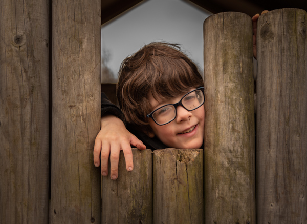 boy in glasses at a gap in a fence