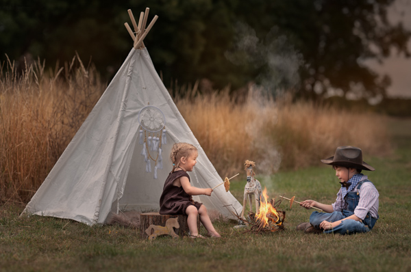 children camping and cooking at a fire
