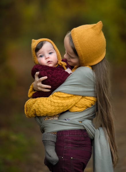 young girl holding a baby in an outdoor photoshoot