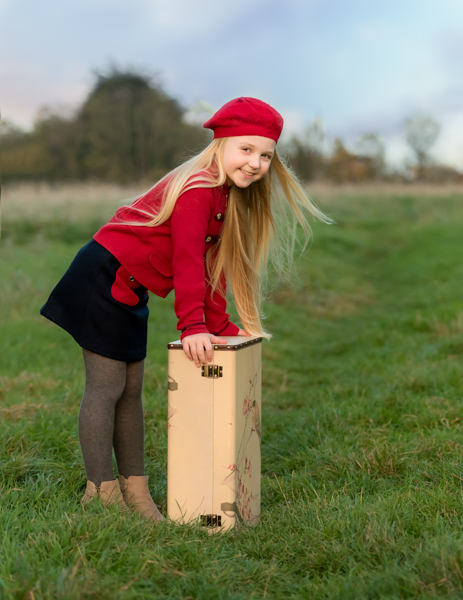 girl in a field with a suitcase