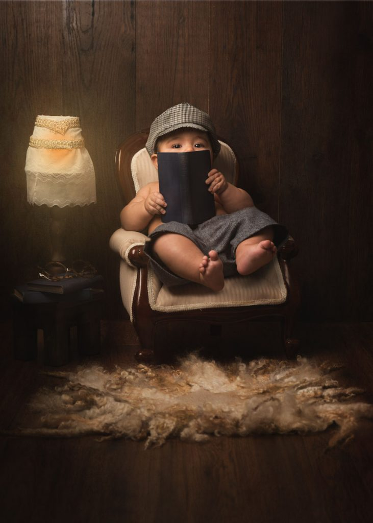 cute baby reading a book in a childrens photography sitter session