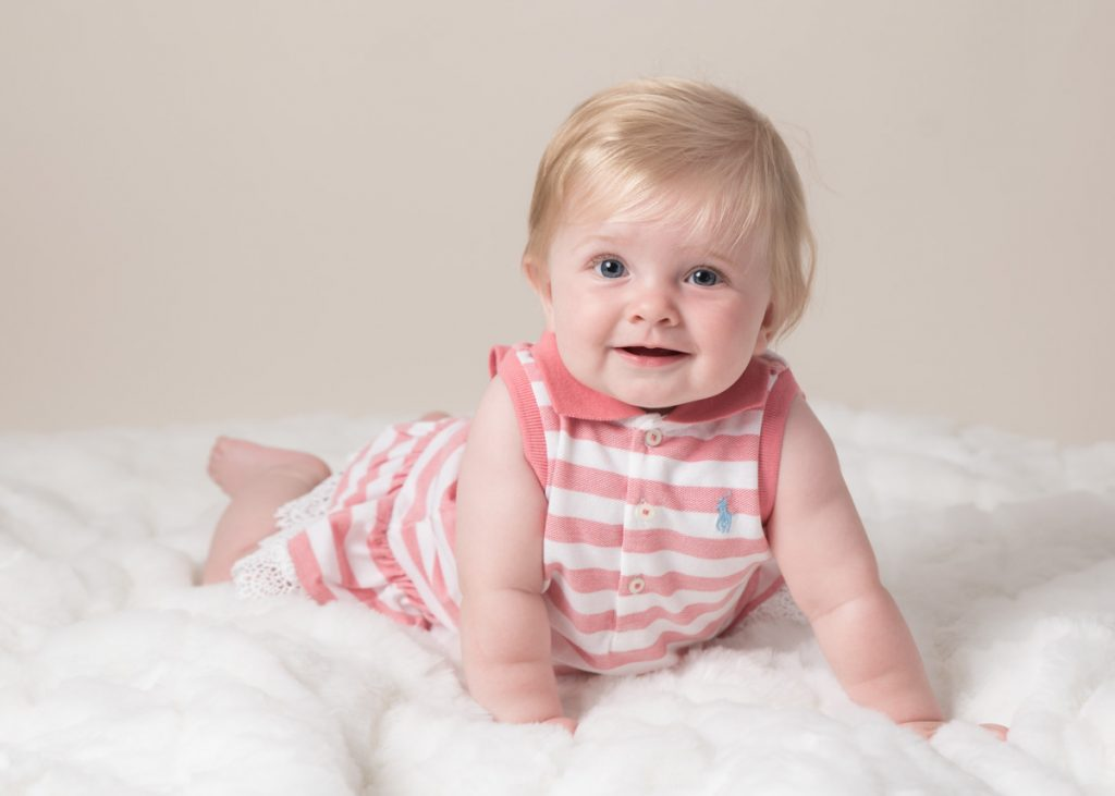 Cute little girl on a soft pillow cloud having her sitter session